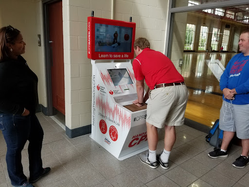 A man using the AHA CPR Training Kiosk in an airport