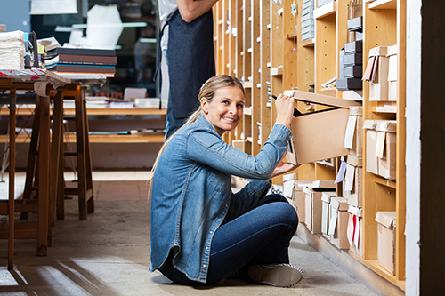 A woman pulls a box off of the shelf