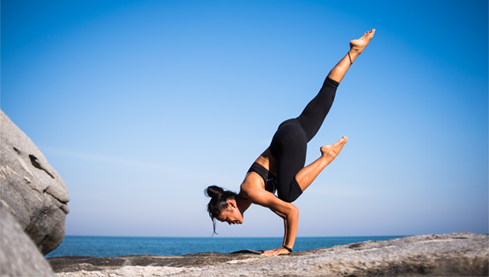 A healthy woman doing a yoga pose outside